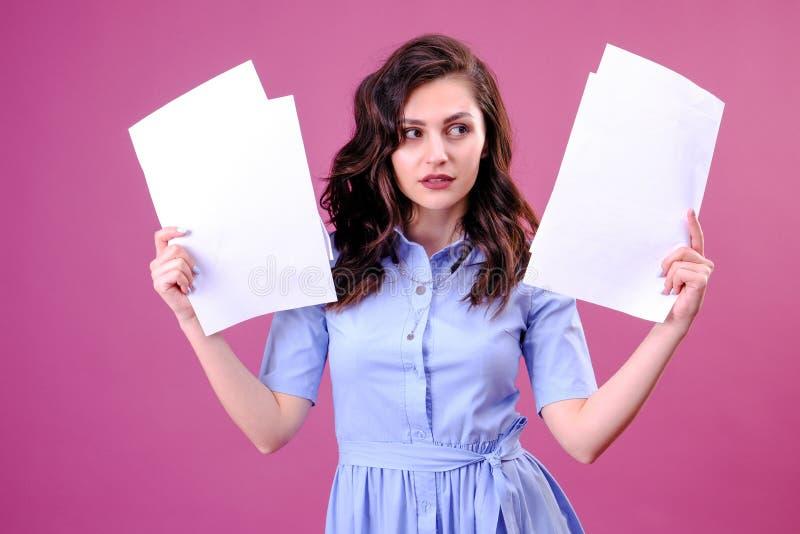 拿着在桃红色背景的年轻白种人妇女纸惊吓在与惊奇面孔的震动,害怕和激发充满恐惧 免版税图库摄影
