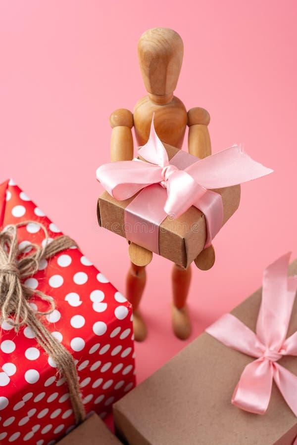 拿着在桃红色背景的木玩具模型礼物 假日卡片为情人节和妇女的天 库存图片