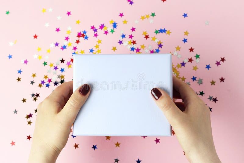 拿着在桃红色背景,顶视图的女性手一个礼物盒 库存照片