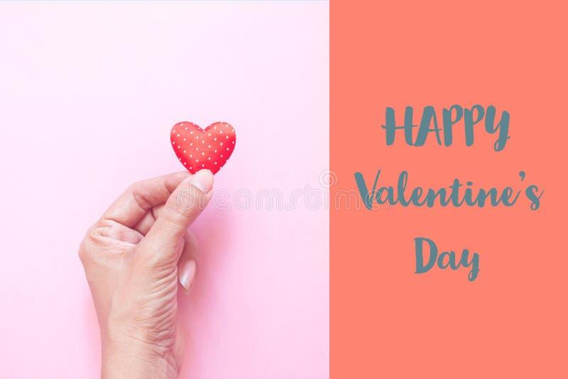 拿着在桃红色颜色背景的妇女的手微型圆点心脏 日愉快的s华伦泰 免版税库存图片