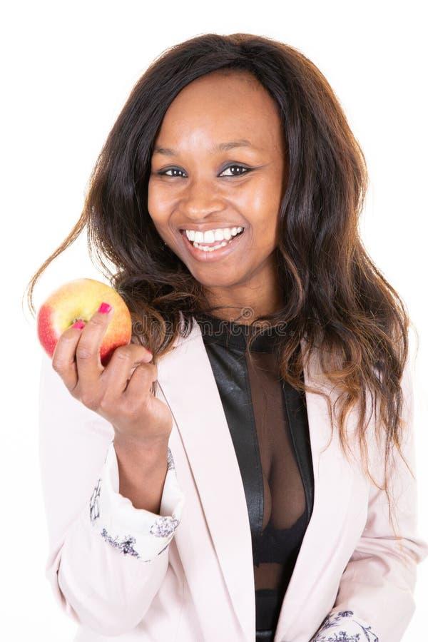 拿着在棕榈手上的可爱的快乐的性感的非洲妇女大红色苹果 免版税库存照片