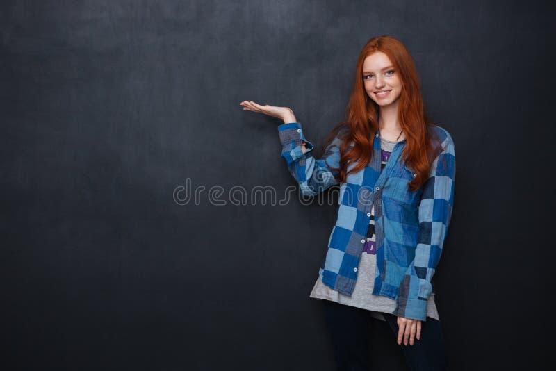 拿着在棕榈的微笑的妇女copyspace在黑板背景 库存图片