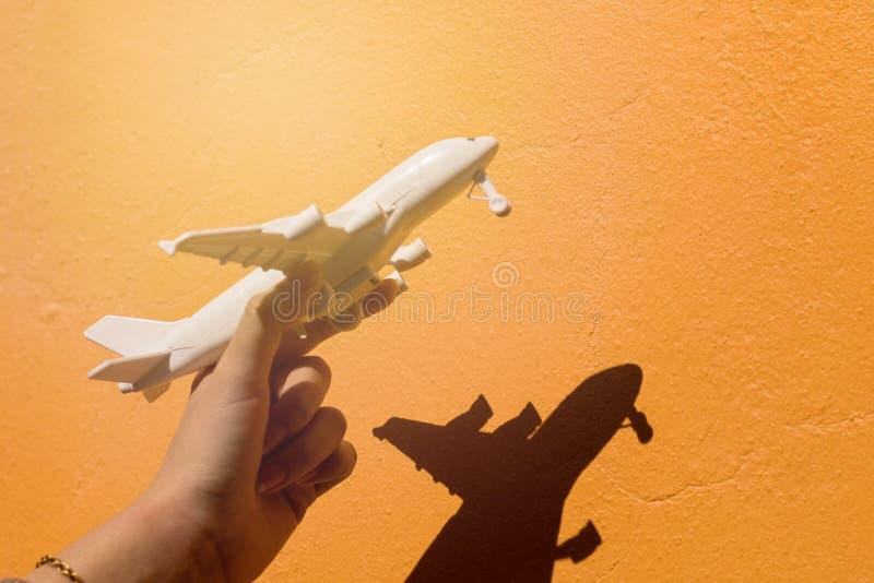 拿着在橙色墙壁背景的手的阴影飞机模型 库存图片