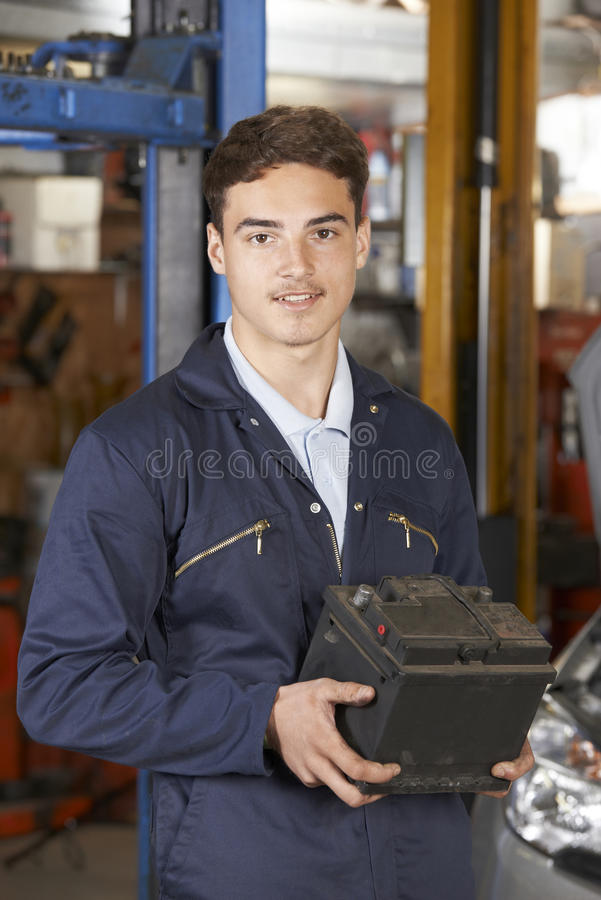 拿着在汽车修理店的学徒技工汽车电池 免版税库存照片
