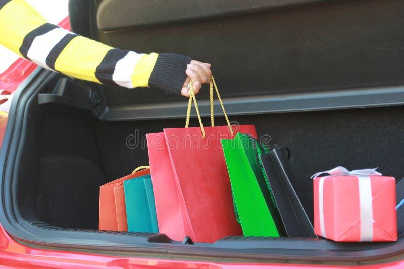 拿着在汽车的妇女手特写镜头购物带来 免版税库存照片