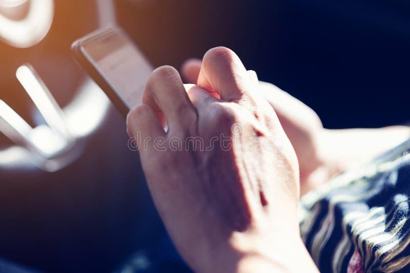 拿着在汽车里面的人的手智能手机 被定调子的作用 库存图片