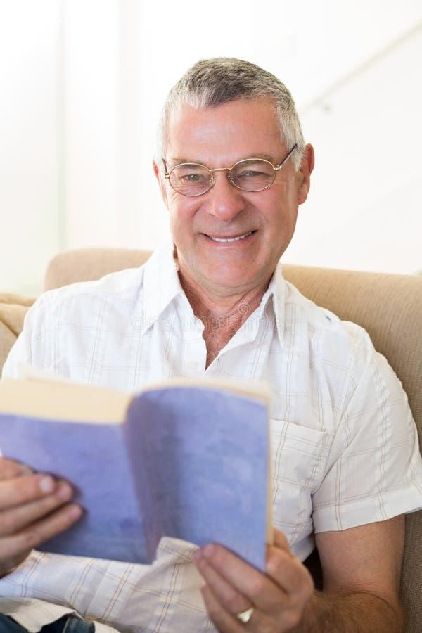 拿着在沙发的老人书 免版税库存照片