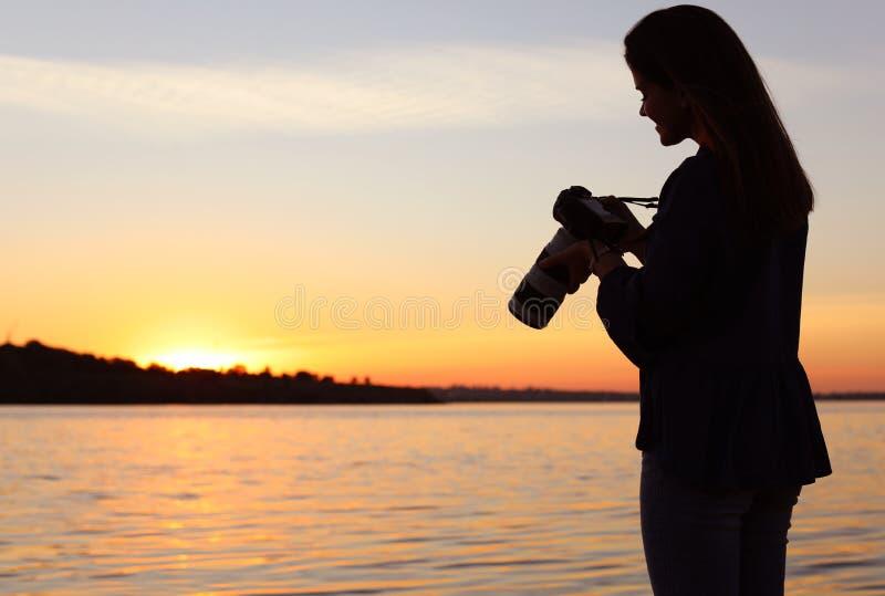 拿着在河沿的年轻女性摄影师专业照相机 库存图片