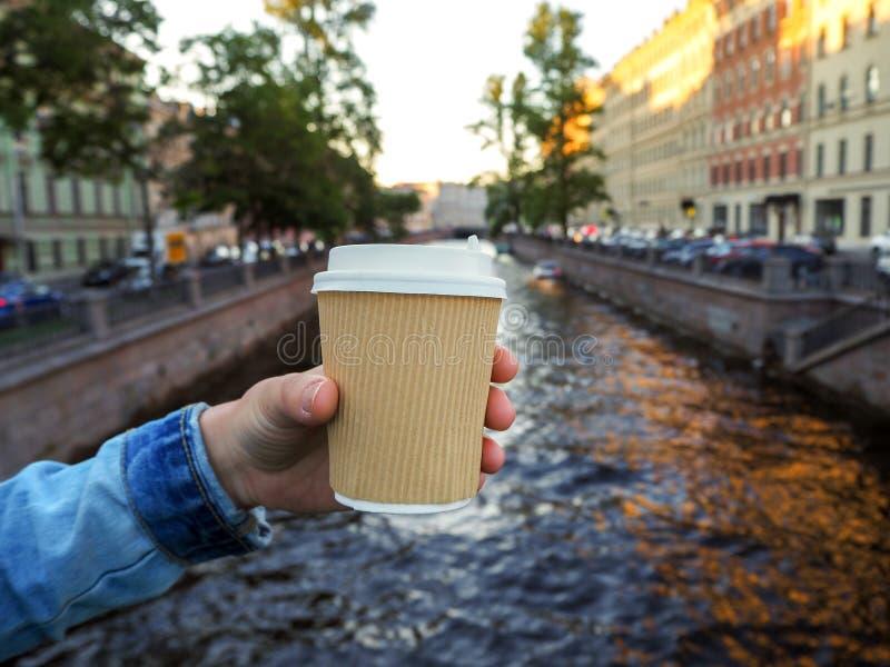 拿着在河背景的女性手大模型一个咖啡纸外带的杯子与拷贝空间 免版税图库摄影