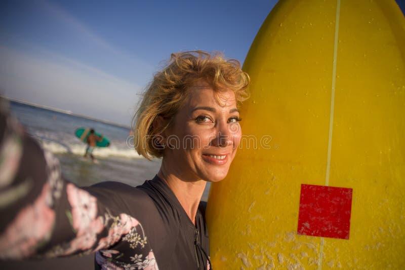 拿着在海滩的泳装的年轻可爱和愉快的白肤金发的冲浪者妇女水橇板采取自画象selfie图片smi 图库摄影