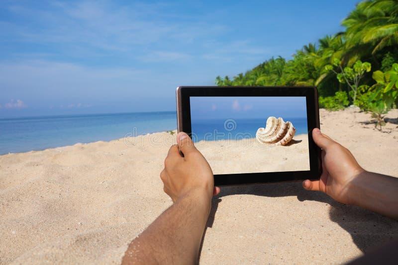 拿着在海滩的现有量片剂个人计算机 免版税库存照片