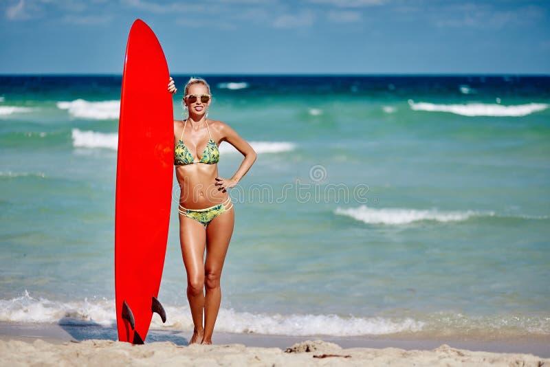 拿着在海边海滩的年轻俏丽的妇女冲浪板-充分len 免版税图库摄影