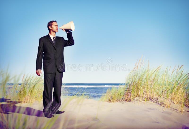 拿着在海滩概念的商人扩音器 图库摄影