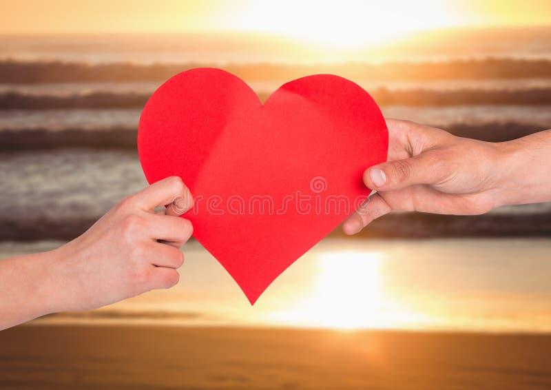 拿着在海滩的夫妇的手红色心脏 免版税库存照片
