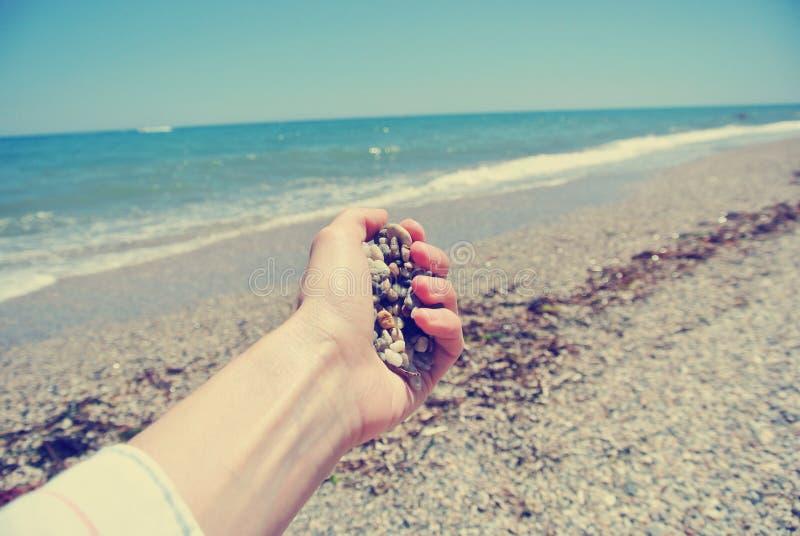 拿着在海滩的女性手小卵石,减速火箭/葡萄酒 库存图片