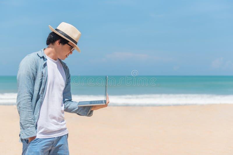 拿着在海滩的年轻亚裔人膝上型计算机 免版税库存图片