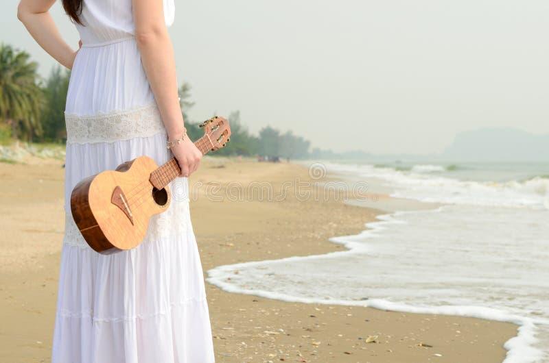 拿着在海滩的年轻亚裔女孩尤克里里琴 免版税库存图片