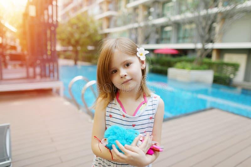 拿着在游泳池和公寓背景的逗人喜爱的小孩玩具  免版税图库摄影