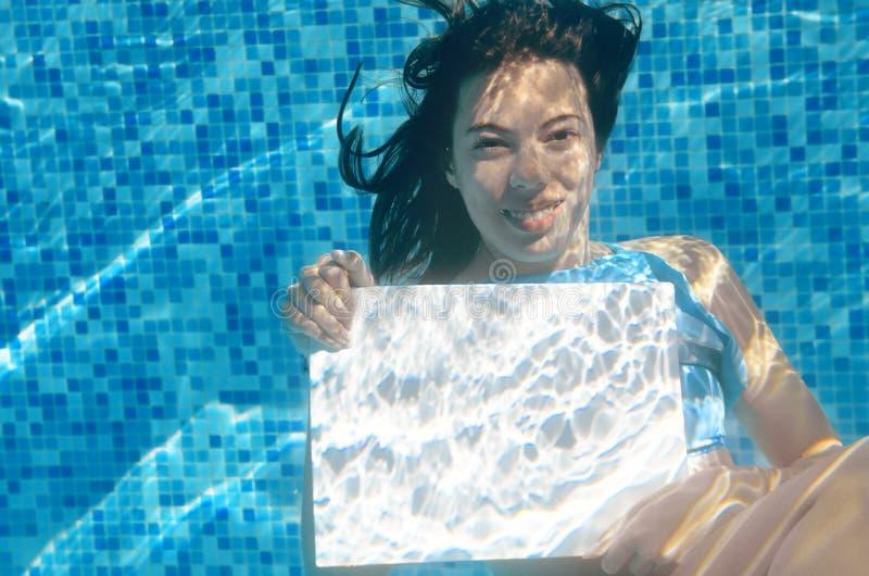 拿着在游泳池的美丽的女孩白色空白的板在水下,家庭度假 免版税库存图片