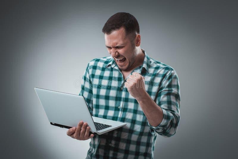 拿着在灰色背景的商人一台膝上型计算机 免版税库存照片