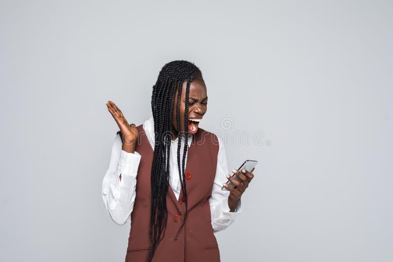 拿着在灰色背景的震惊年轻非洲妇女画象手机 免版税库存照片