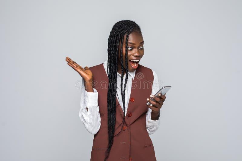 拿着在灰色背景的震惊年轻非洲妇女画象手机 库存图片