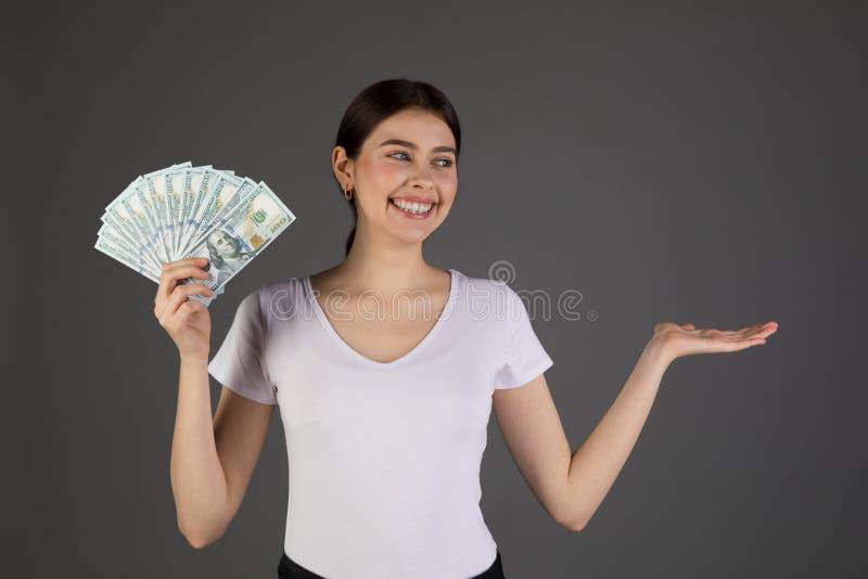 拿着在灰色背景的eurupean妇女接近的画象金钱 免版税库存图片