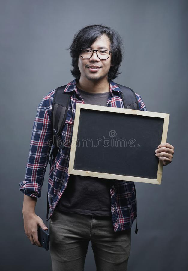 拿着在灰色Bac的亚裔大学生画象黑板 免版税库存照片