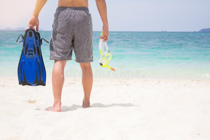 拿着在热带的人假期后侧方潜航的齿轮  图库摄影