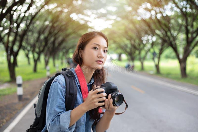 拿着在狂放的妇女摄影师一台照相机为拍旅游旅客的照片 图库摄影