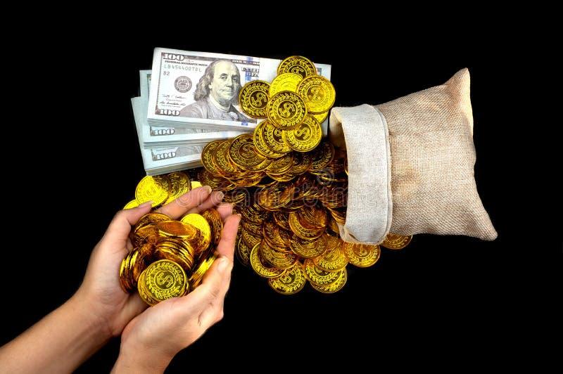 拿着在珍宝大袋和堆捆绑的手金币100张美元钞票 图库摄影