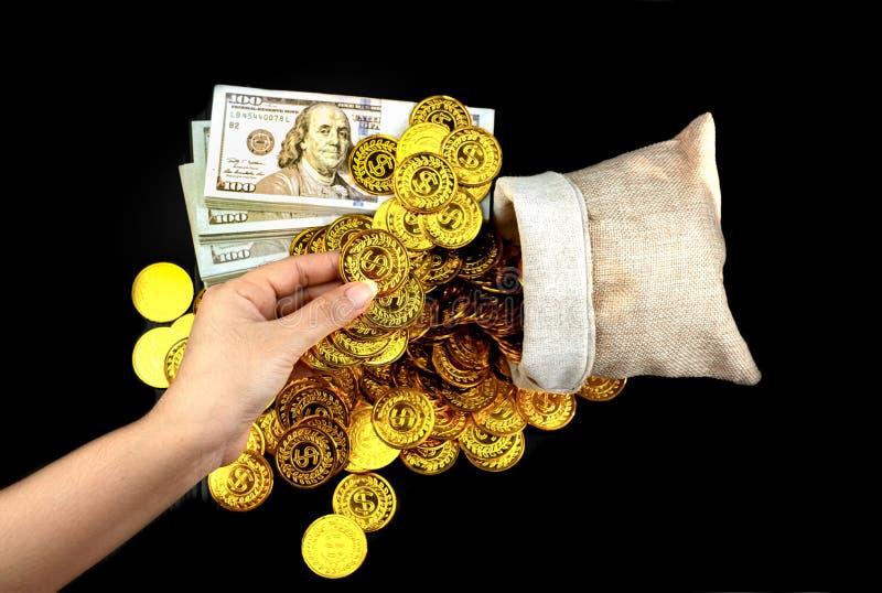 拿着在珍宝大袋和堆捆绑的手金币100张美元钞票 免版税图库摄影