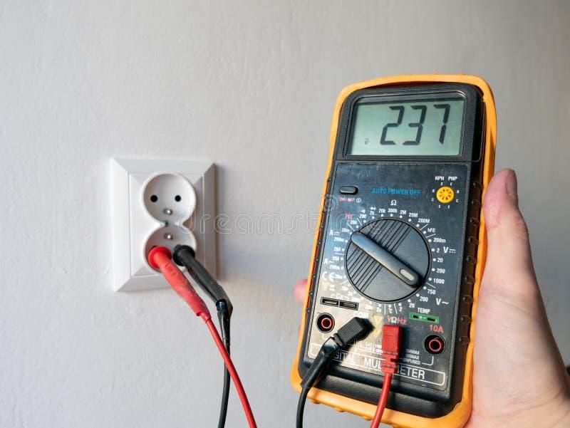 拿着在电源插座前面的手一个电多用电表 库存照片