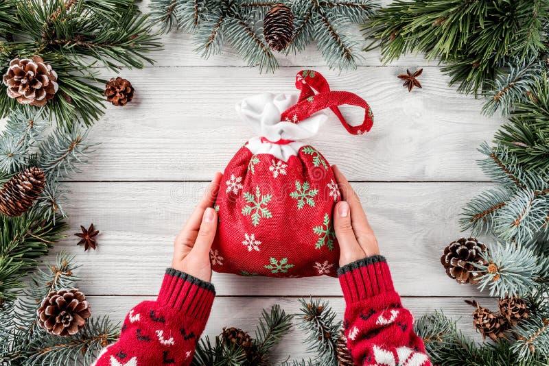拿着在白色木背景的女性手圣诞节红色袋子与冷杉分支和杉木锥体 Xmas和新年题材 免版税库存图片