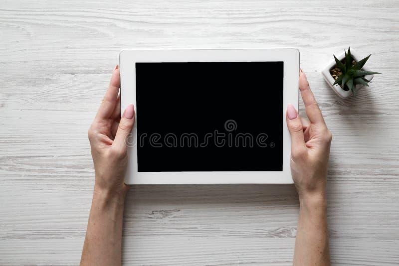 拿着在白色木表面,顶上的看法的女性手片剂 顶视图,从上面 库存图片