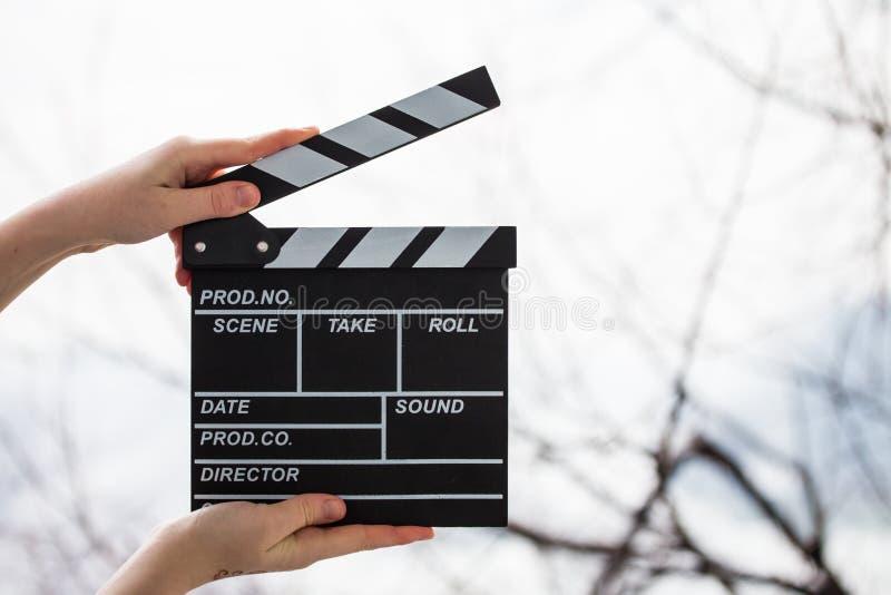 拿着在白色的女性手电影拍板 免版税库存照片