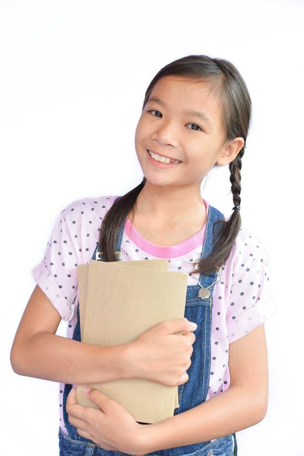 拿着在白色的小亚裔女孩画象一本书 库存图片