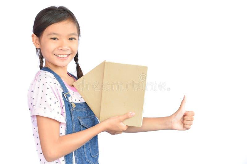 拿着在白色的小亚裔女孩画象一本书 库存照片