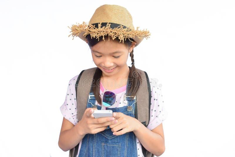 拿着在白色的小亚裔女孩画象智能手机 免版税库存照片