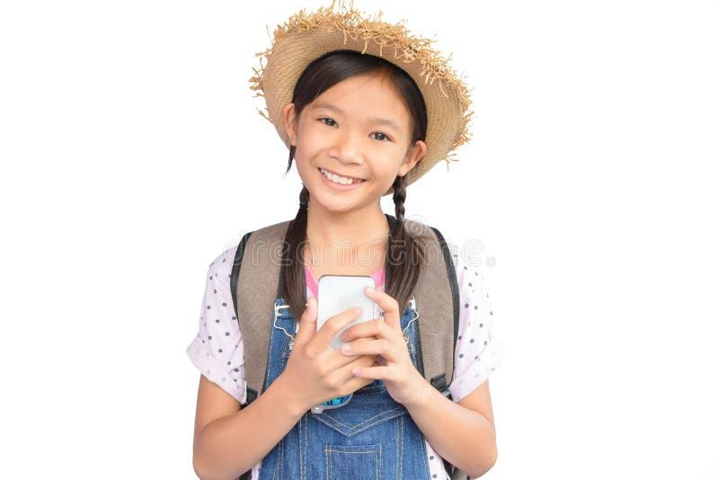 拿着在白色的小亚裔女孩画象智能手机 免版税库存图片