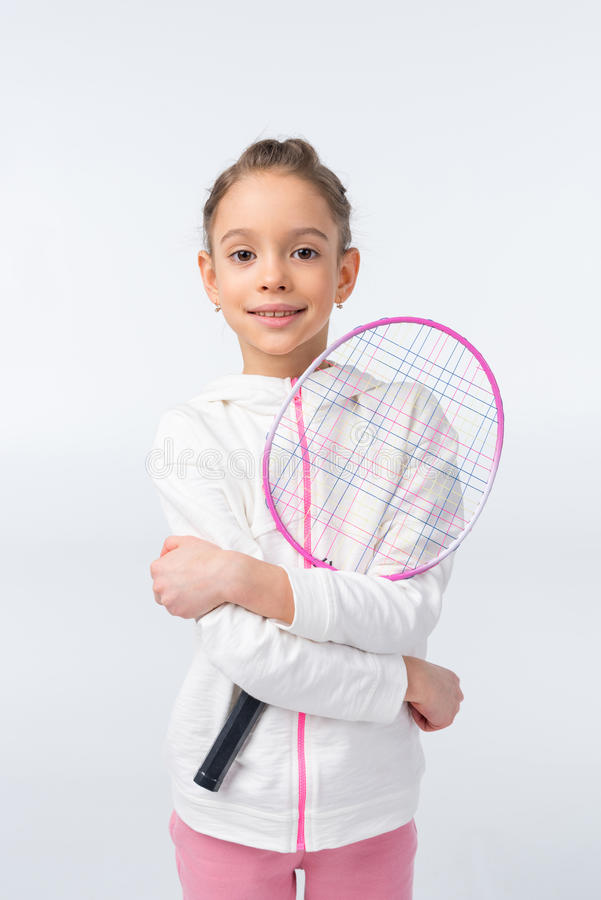拿着在白色的微笑的女孩羽毛球拍 免版税库存图片