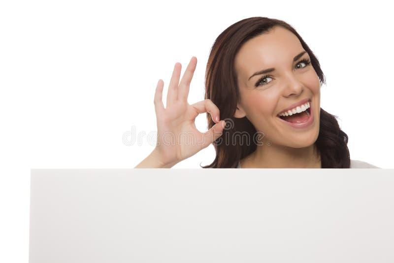 拿着在白色的微笑的混合的族种女性空白的标志 免版税库存照片