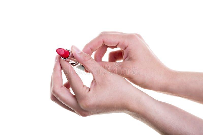 拿着在白色背景的女性手红色唇膏 库存照片