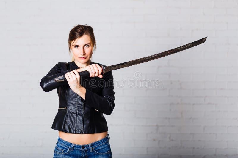 拿着在白色背景的妇女日本武士剑 艺术女孩军事silueta向量 库存照片