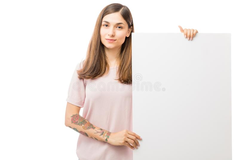 拿着在白色背景的妇女空白的广告牌 免版税库存照片