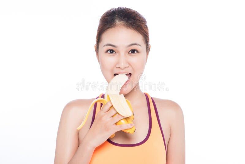 拿着在白色背景的微笑的运动的亚裔妇女香蕉 库存照片