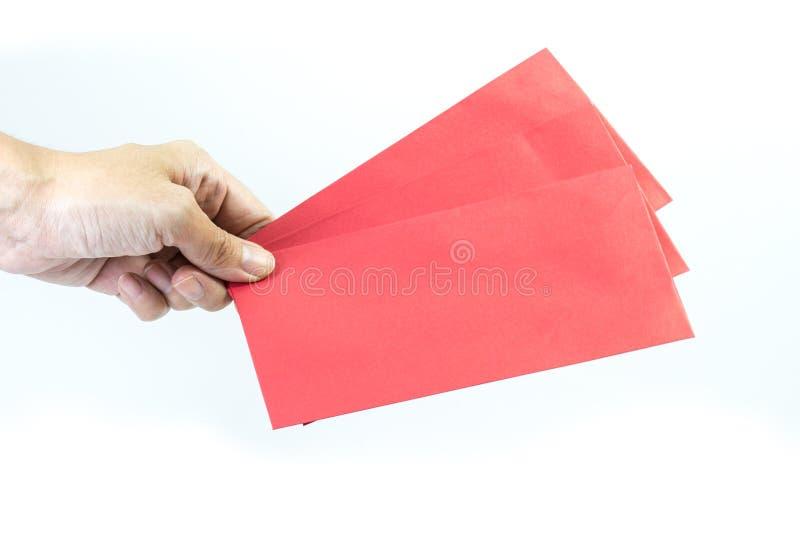 拿着在白色背景的手红色信封 免版税图库摄影