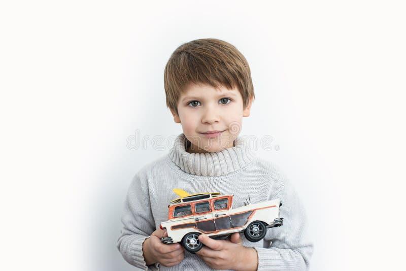 拿着在白色背景的男孩一辆玩具减速火箭的汽车 免版税库存图片