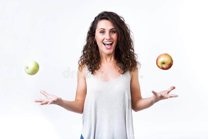 拿着在白色背景的美丽的少妇绿色和红色苹果 库存照片