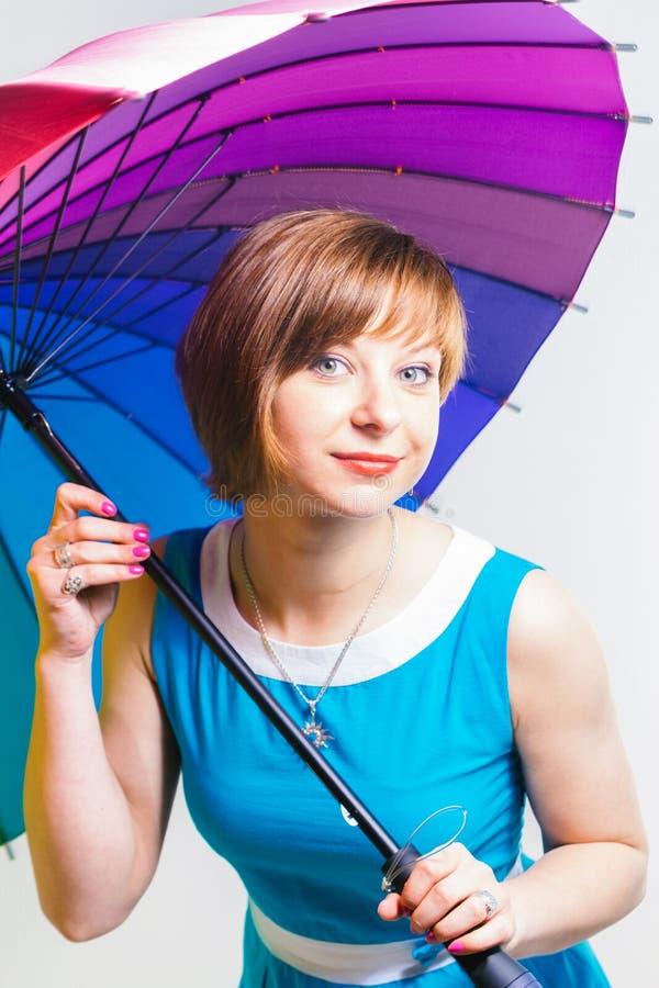 拿着在白色背景的蓝色礼服的可爱的女孩五颜六色的正面彩虹伞 工作室射击,复制空间 库存照片